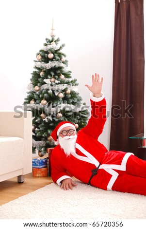 Santa claus laying on floor at home, waving with one hand, in front of christmas tree