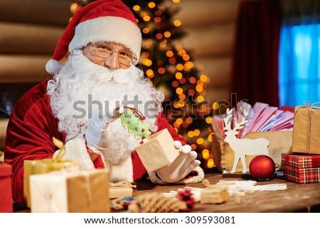 Santa Claus looking at camera while putting gift into small box - stock photo