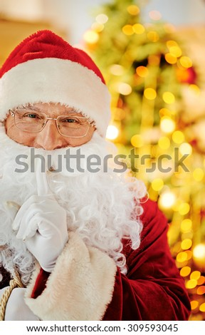 Santa Claus looking at camera with his forefinger by mouth - stock photo