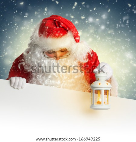 Santa Claus looking down on white blank banner holding a shining lantern