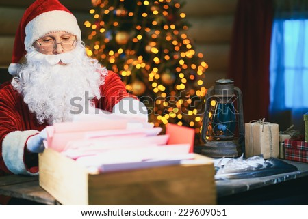 Santa Claus looking through Christmas letters - stock photo
