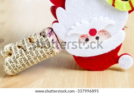 Santa Claus lying down next to cork wine cap.