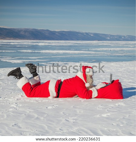 Santa Claus lying on the snow, looking at laptop news, shooting was conducted in a sunny day on lake Baikal - stock photo