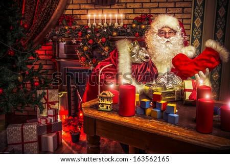 Santa Claus making Christmas gifts at home. - stock photo
