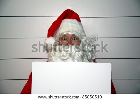 Santa Claus Mugshot. Santa holds a blank white booking sign while his mugshot is taken. Booking Sign is blank for your text. - stock photo