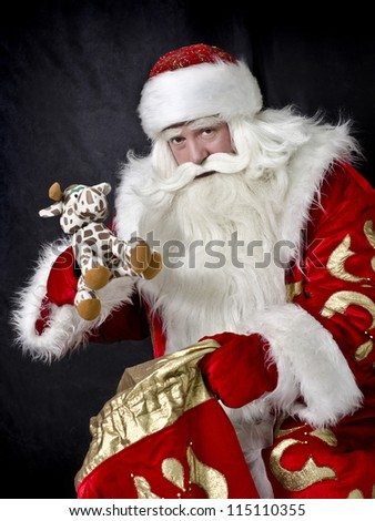 Santa Claus on a black background gives a gift - stock photo