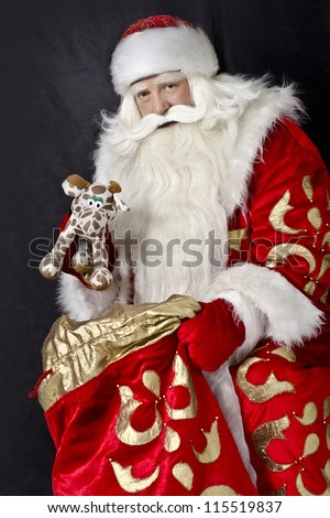 Santa Claus on a black background gives a gift out of the bag