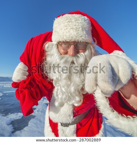 Santa Claus on a frozen lake on a sunny winter day, smiling for the camera - stock photo