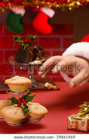 Santa Claus on Christmas eve reaching for a mince pie - stock photo