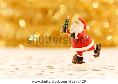 Santa Claus on skates holding a Christmas tree on blurred golden background - stock photo