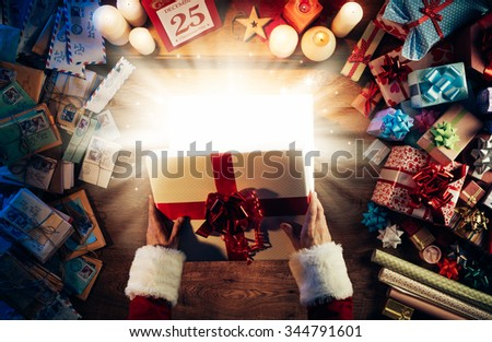 Santa Claus opening a magic bright Christmas gift box, presents and letters all around, hands top view - stock photo