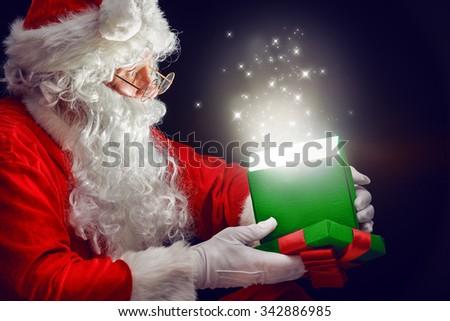 Santa Claus opening a magic gift box. - stock photo