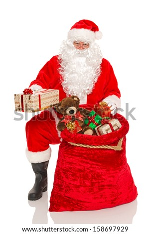 Santa Claus or Father Christmas handing out gifts from his sack, isolated on a white background. - stock photo