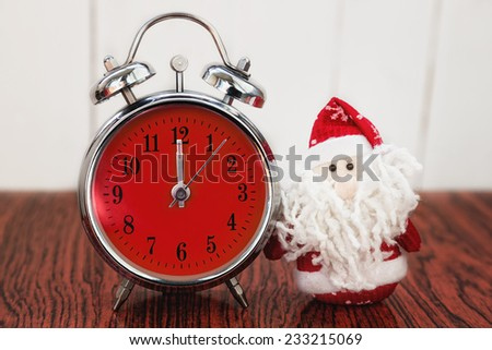 Santa Claus or Father Frost and vintage alarm clock with red dial on wooden background. Showing time twelve midnight - stock photo