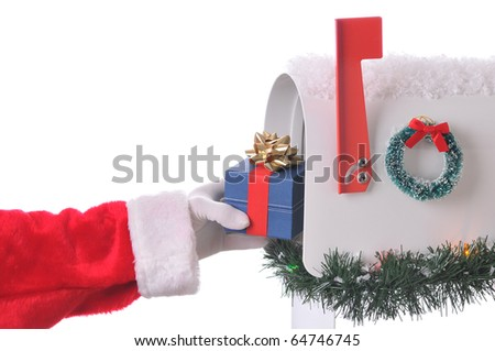 Santa Claus placing a Christmas present into an open Mailbox decorated for the holidays isolated on white. Horizontal composition with only hand and arm visible. - stock photo