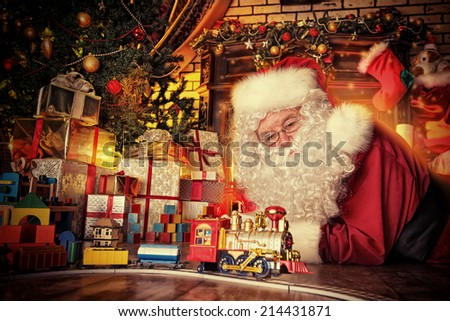 Santa Claus playing with toys under the Christmas tree. - stock photo