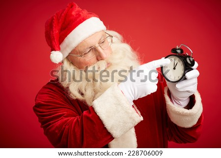 Santa Claus pointing at alarm clock showing five minutes to twelve - stock photo
