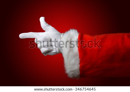 Santa Claus pointing, hand and arm only  over a light to dark red background