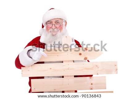 Santa Claus pointing in blank wooden sing, isolated on white background - stock photo