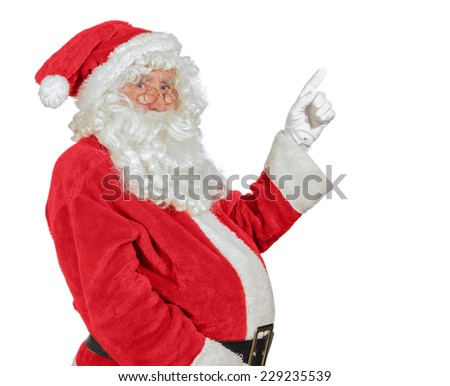 Santa Claus pointing in gloved hand with white copy space for advertising - stock photo