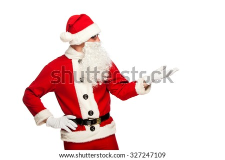 Santa Claus pointing in white blank sign with smile, isolated on white background - stock photo