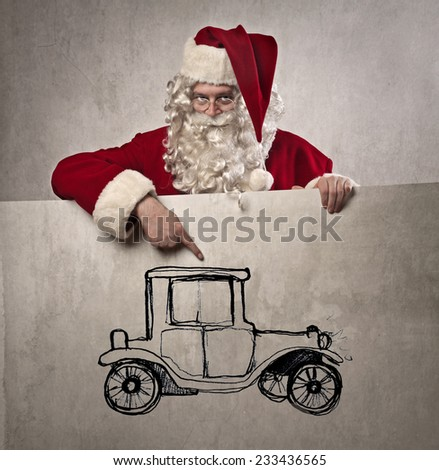 Santa Claus pointing out the picture of an old-fashioned car  - stock photo