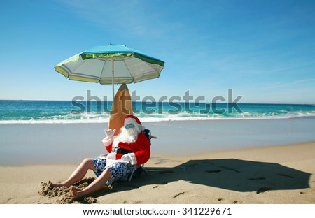 Santa Claus Poses with his Surf Board while on a Beach with the turquoise blue ocean and waves in the background. Santa Claus loves the beach. Focus on Santa's Face.  - stock photo