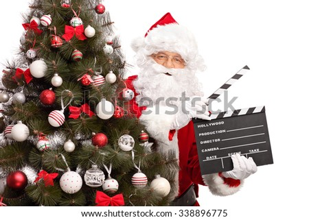 Santa Claus posing behind a Christmas tree and holding a movie clapperboard isolated on white background - stock photo