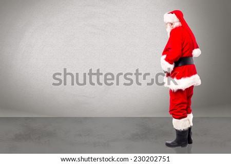Santa claus posing sideways and looking at something - stock photo