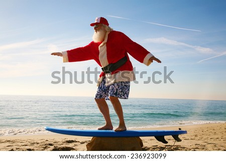 Santa Claus practices his Surfing Skills on his Surf Board on the beach, before he goes into the ocean. Santa Loves the Beach when on vacation from delivering gifts to good boys and girls at christmas - stock photo