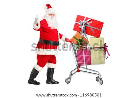 Santa Claus pushing a shopping cart full of gifts and giving a thumb up isolated on white background - stock photo