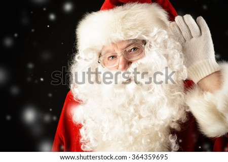 Santa Claus put his hand to his ear and listens to something. Christmas time. Black background. - stock photo