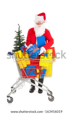 Santa Claus putting a gift in shopping cart full luxury presents and tree - stock photo