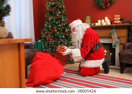 Santa Claus putting gifts under Christmas tree