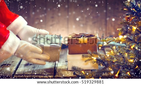 Santa Claus putting gifts under the Christmas tree with blinking garlands. Santa Claus giving gift box, holding a gift in his hands over wooden background.