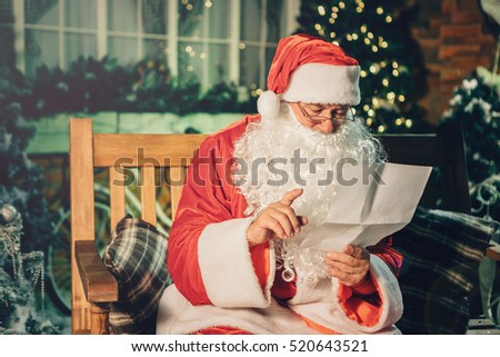 Santa claus read letter from children over living room, christmas tree. Happy santa writing list with a quill at home.Holidays, childhood and people concept