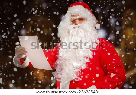 Santa Claus reading a letter outdoors - stock photo