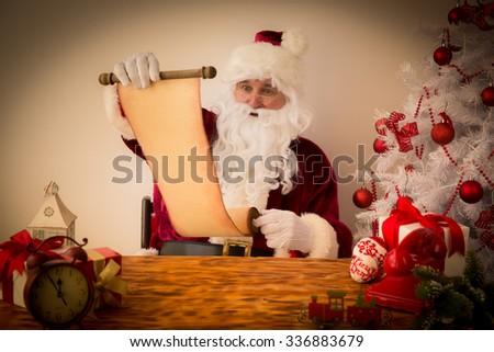 Santa Claus reading scroll. Christmas holiday concept - stock photo