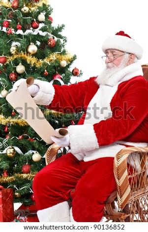 Santa Claus reading wish list, sitting in rocking chair next  Christmas tree, isolated on white background - stock photo