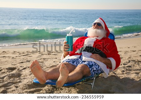 Santa Claus relaxing in his lounge chair on a tropical sandy beach - Christmas concept  Santa Claus loves to vacation when not having to work on Christmas Eve delivering gifts to good boys and girls. - stock photo