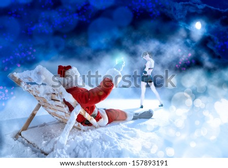 Santa Claus relaxing in the snow field using sunbed - stock photo