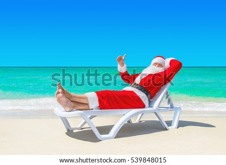 Santa Claus relaxing thumbs up gesturing on sunlounger at ocean tropical sandy beach against turquoise waves. Merry Christmas and Happy New Year travel destinations for tropical vacations concept.