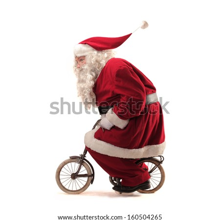 Santa Claus rides a bicycle - stock photo