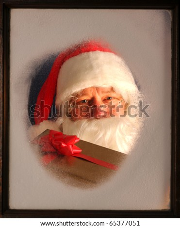 Santa Claus seen through a frosted window holding up a wrapped present.