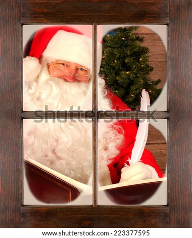 Santa Claus seen through a frosty window checking his list. He is holding a large book and a quill pen. The window fills the frame.