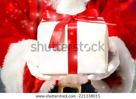 Santa Claus Showing a Christmas Gift Box - stock photo