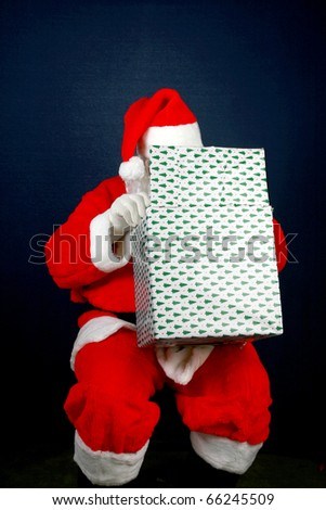 Santa Claus shows his sence of humor by looking inside a christmas present box on top of his head - stock photo