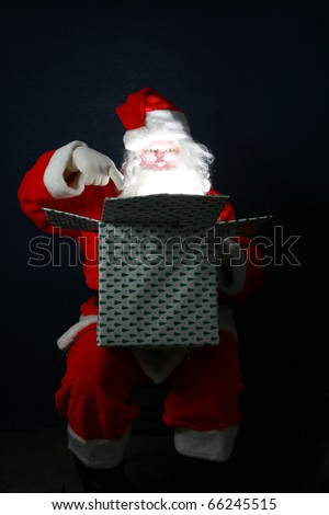 Santa Claus shows his sence of humor by looking inside a christmas present box on top of his head