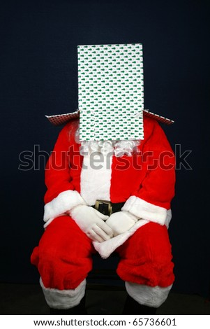 Santa Claus shows his sence of humor by looking inside and wearing a christmas present box on top of his head - stock photo