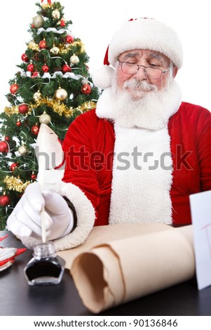 Santa Claus sitting at  desk, writing a list of all the boys and girls who will get Christmas presents , isolated on white background - stock photo